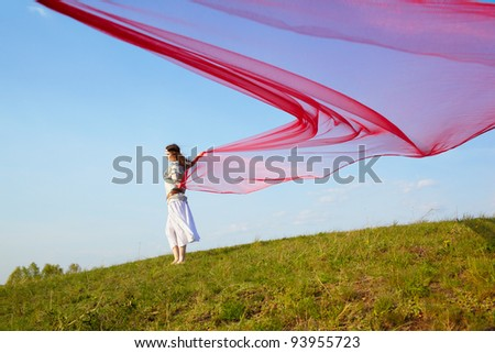 outdoor portrait of beautiful hippie girl running with big piece of red light cloth under the blue sky