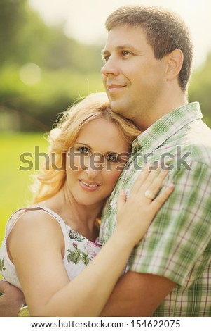 Outdoor portrait of beautiful married couple hugging each other