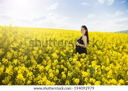 Outdoor portrait of beautiful pregnant woman posing in yellow colza field - stock photo