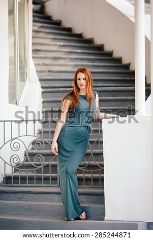 Outdoor portrait of beautiful redhead young woman near column