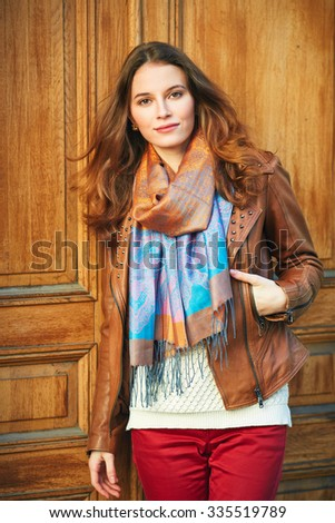 Outdoor portrait of beautiful redhead young woman near door