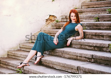 Outdoor portrait of beautiful redhead young woman on the stairs - stock photo