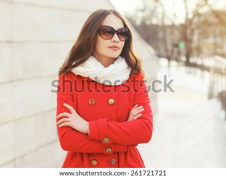 Outdoor portrait of beautiful woman in sunglasses and red jacket