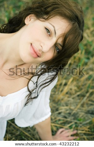 Outdoor portrait of beautiful woman in the field with wavy hair - stock photo