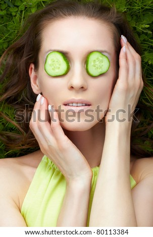 outdoor portrait of beautiful woman laying on green grass with slices of cucumber on eyes