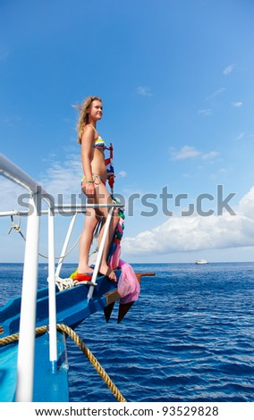 outdoor portrait of beautiful young blonde woman in bikini on yacht's prow - stock photo