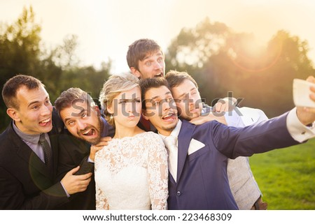 Outdoor portrait of beautiful young bride with groom and his friends taking selfie - stock photo