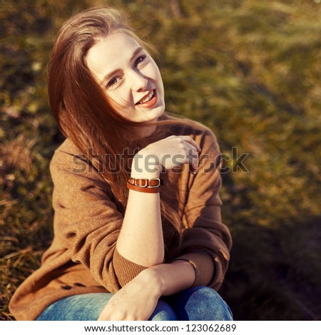 Outdoor portrait of beautiful young brunette in spring in the park. - stock photo