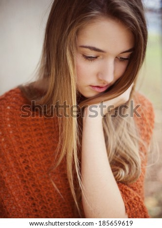 Outdoor portrait of beautiful young sad girl thinking about something - stock photo
