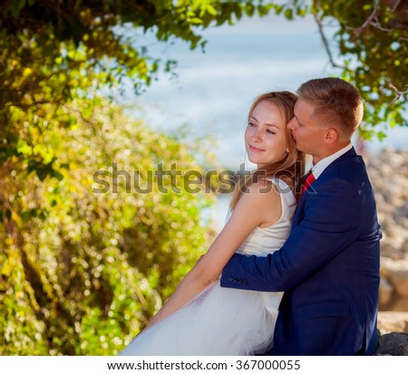 Outdoor portrait of beautiful young wedding couple - stock photo