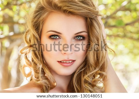 Outdoor portrait of beautiful young woman against sunny forest - stock photo