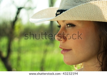 Outdoor portrait of beautiful young woman cowgirl in hat