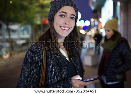Outdoor portrait of beautiful young woman using her mobile phone at night. - stock photo