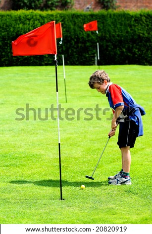 outdoor portrait of boy playing mini golf - stock photo