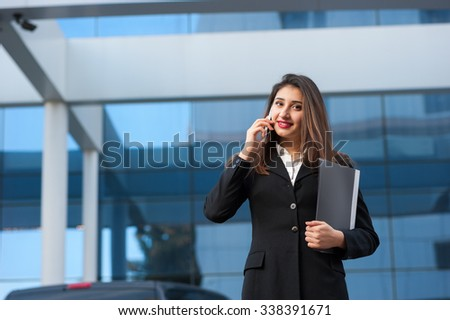 Outdoor portrait of business woman talking at the phone with modern building as background. - stock photo