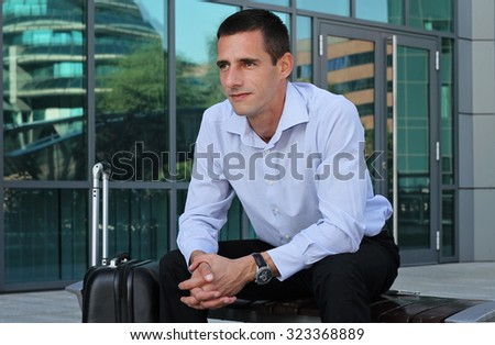 Outdoor portrait of businessman in front of modern  building. Businessman with suitcase, business trip concept