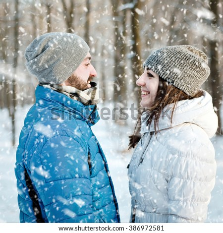 Outdoor portrait of cheerful handsome bearded man and pretty girl enjoying the snowfall in winter forest. Young happy couple in love. Christmas holidays, New Year, Valentine's day. - stock photo
