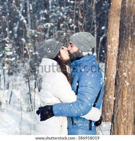 Outdoor portrait of cheerful handsome bearded man kissing pretty girl and enjoying the snowfall in winter forest. Young couple in love. Christmas holidays, New Year, Valentine's day. - stock photo
