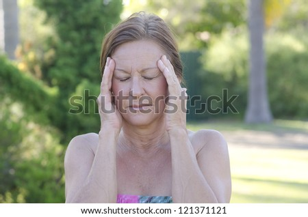Outdoor portrait of concerned mature woman with headache and hands at forehead, isolated with blurred background. - stock photo