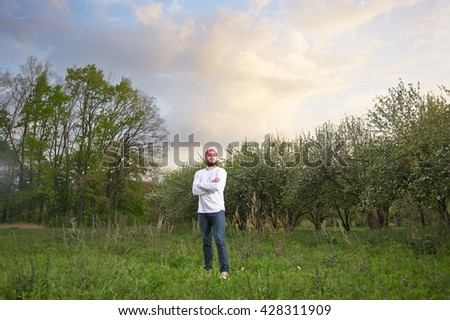 Outdoor portrait of confident bearded young man standing in park in sunset time. - stock photo