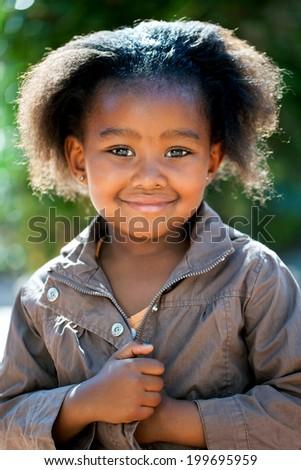 Outdoor portrait of cute African girl wearing brown jacket. - stock photo