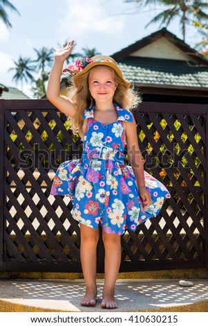 Outdoor portrait of cute little girl in blue floral dress and beach straw hat. Beautiful lady waving her hand and smile. Summer sunny day. House with wooden fence at tropical background. Mothers day. - stock photo