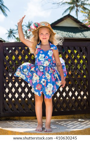 Outdoor portrait of cute little girl in blue floral dress and beach straw hat. Beautiful lady waving her hand and smile to the camera. Summer sunny day. House with wooden fence at tropical background. - stock photo