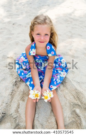 Outdoor portrait of cute small blonde girl in floral dress sitting on the beach sand. Little lady hold frangipani tropical flowers and smiles to the camera. Summer sunny day. Happy Mothers day. - stock photo