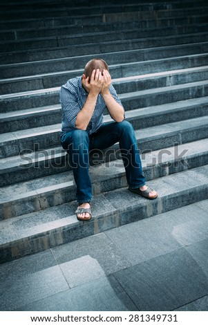 Outdoor portrait of despaired young man covering his face with hands sitting on stairs. Feelings of sadness, despair and tragedy - stock photo