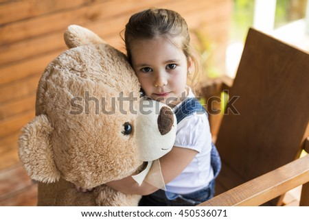 Outdoor portrait of expressive charming little girl hugging huge plush bear. Little girl playing with teddy bear - stock photo