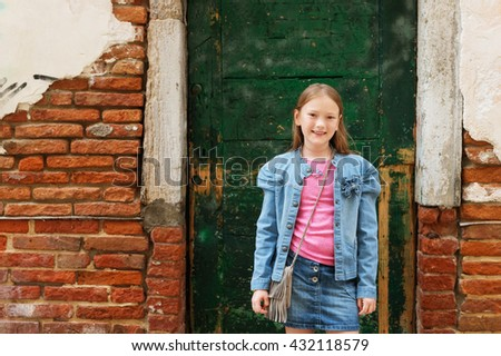 Outdoor portrait of fashion little girl of 7-8 years old, wearing denim skirt and jacket, standing against old facade. Young tourist in Italy - stock photo