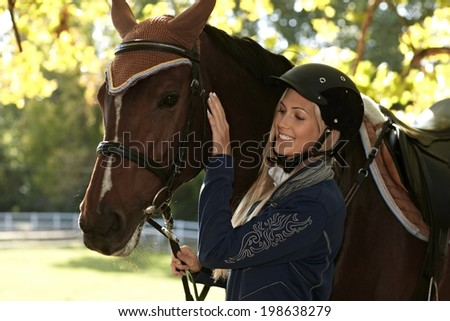 Outdoor portrait of female rider caressing horse. - stock photo