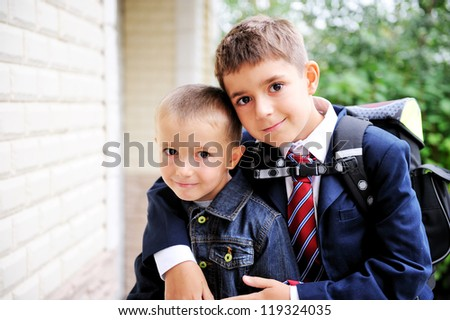 Outdoor portrait of first-grader boy hugging his younger brother - stock photo