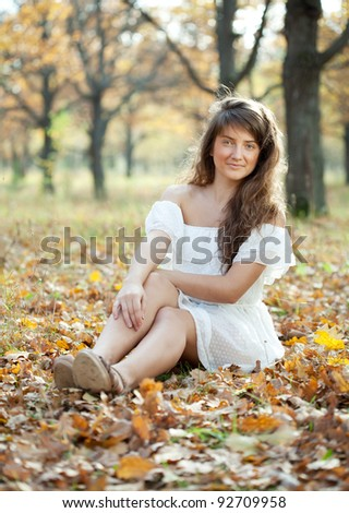 Outdoor portrait of girl in white dress at autumn park