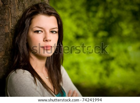 Outdoor portrait of gorgeous young brunette with striking look, serious facial expression.