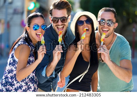 Outdoor portrait of group of friends eating ice cream.