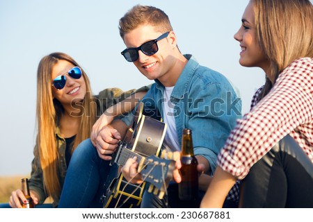 Outdoor portrait of group of friends playing guitar and drinking beer. - stock photo