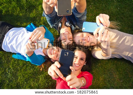 Outdoor portrait of group of friends taking photos with a smartphone in the park - stock photo