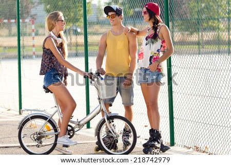 Outdoor portrait of group of friends with roller skates and bike riding in the park. - stock photo