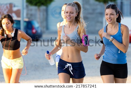 Outdoor portrait of group of women running in the park.  - stock photo