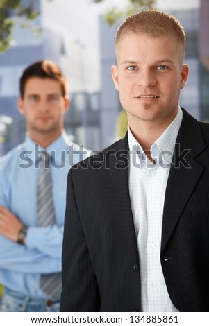 Outdoor portrait of handsome businessman standing outside of office, with colleague in background. - stock photo