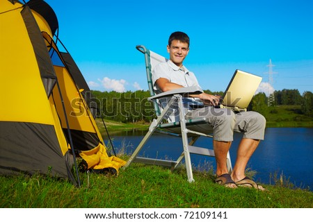 outdoor portrait of handsome man with laptop sitting in folding chair near camp tent - stock photo