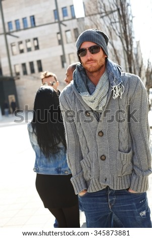 Outdoor portrait of handsome trendy guy wearing scarf, hat and sunglasses. - stock photo