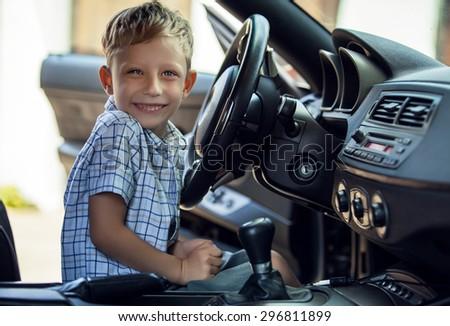 Outdoor portrait of happy blond little boy who explore salon of sport auto.  - stock photo