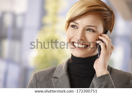 Outdoor portrait of happy businesswoman talking on mobile phone, smiling. - stock photo