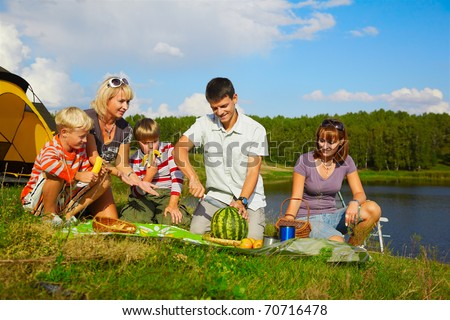 outdoor portrait of happy families at the picnic, young man is cutting watermelon