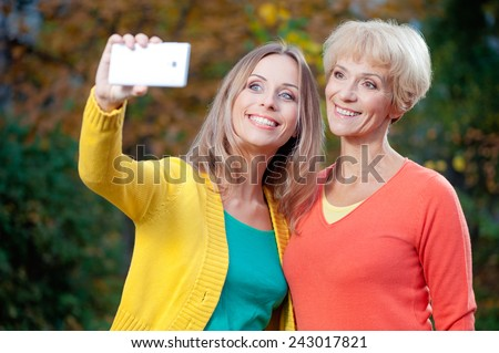 Outdoor portrait of happy middle aged caucasian mother and her adult daughter taking self portrait with white smart phone in the park - stock photo