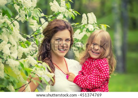 Outdoor portrait of happy mother and daughter in bloomimg flowers