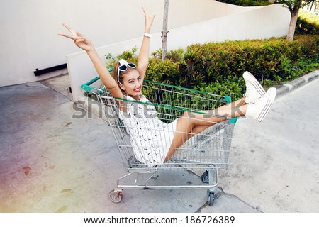 Outdoor portrait of happy smiling blonde woman having fun alone in shopping trolley wearing vintage retro dress and pin up makeup. - stock photo