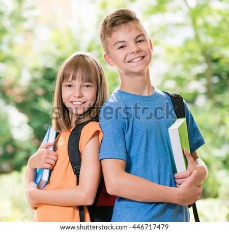 Outdoor portrait of happy teen boy and girl with books. Back to school concept.